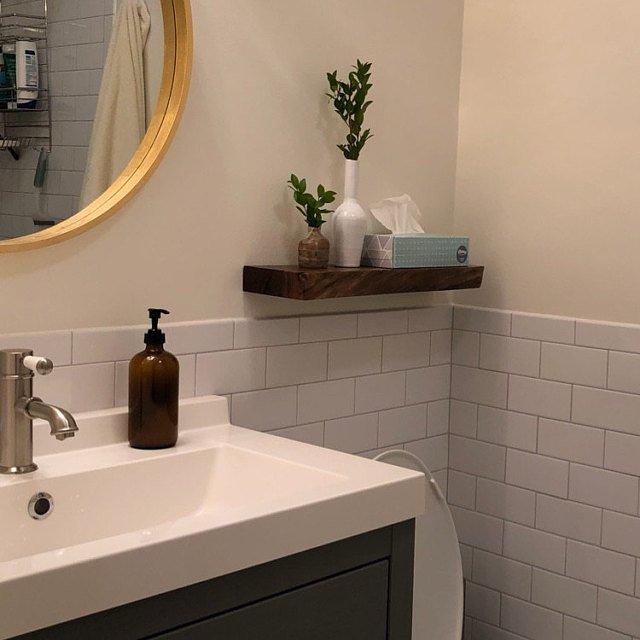 Live edge walnut floating shelf mounted in a bathroom